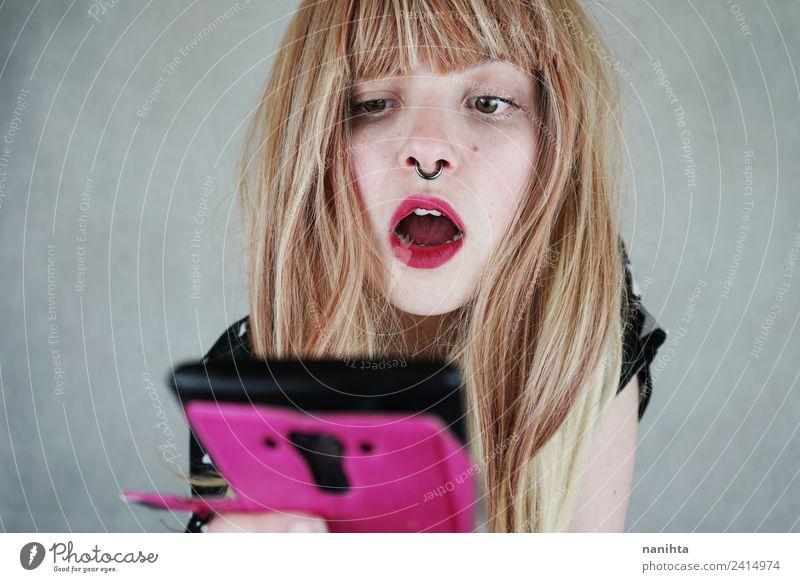 Junge Frau überrascht und schaut auf ihr Handy. Lifestyle Stil schön Haare & Frisuren Haut Gesicht Telefon Technik & Technologie Unterhaltungselektronik