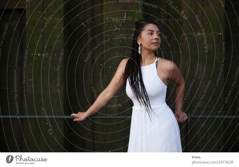Nikolija feminin Frau Erwachsene 1 Mensch Mauer Wand Kleid Ohrringe schwarzhaarig langhaarig Zopf beobachten festhalten Blick stehen dunkel schön Zufriedenheit