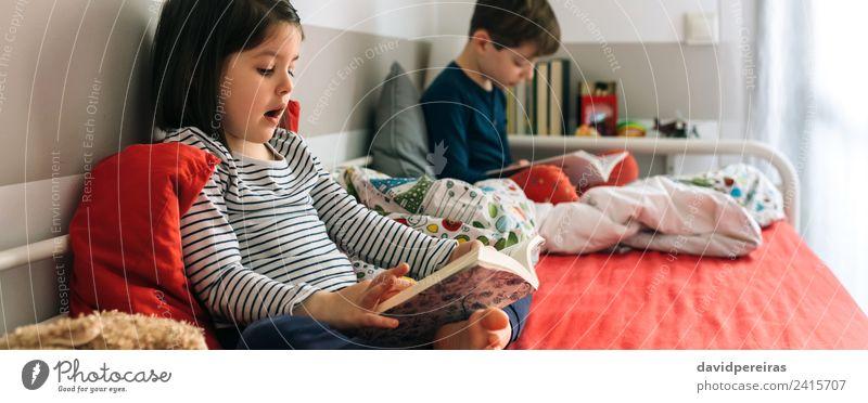 Mädchen und Junge lesen ein Buch auf dem Bett sitzend Lifestyle schön Windstille Schlafzimmer Kind Schule Mensch Frau Erwachsene Mann Schwester Kindheit Hund