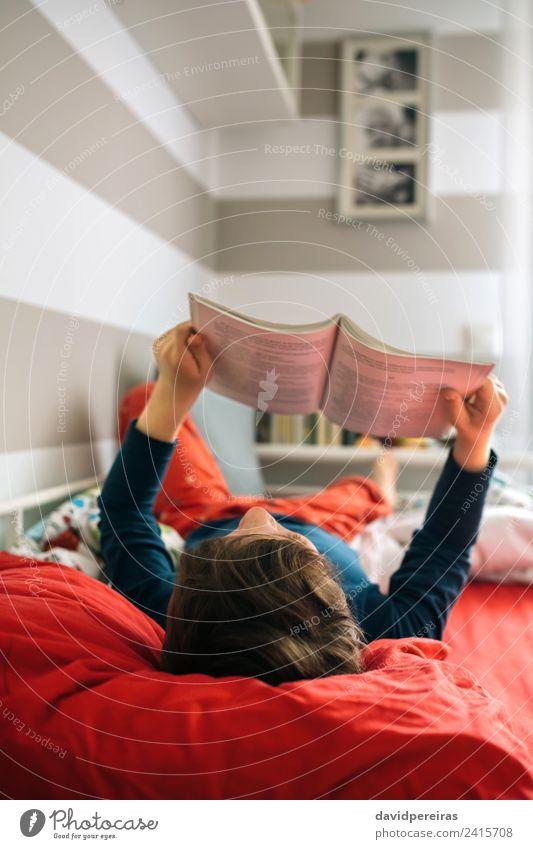 Junge liest auf seinem Bett. Lifestyle Freude schön ruhig Freizeit & Hobby lesen Schlafzimmer Kind Mensch Mann Erwachsene Kultur Buch Spielzeug authentisch