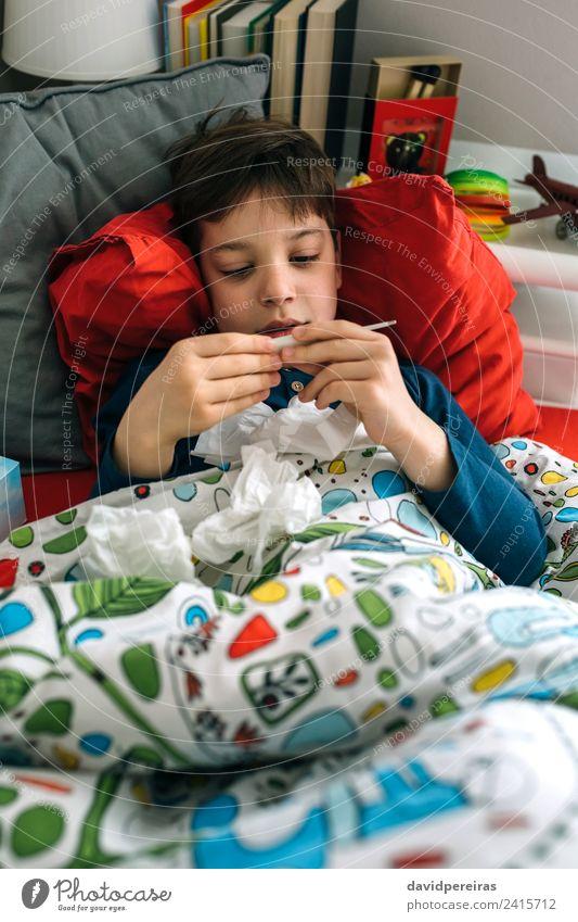 Kaltes Kind schaut auf das Thermometer. Lifestyle Krankheit Lampe Schlafzimmer Mensch Junge Mann Erwachsene Kindheit Buch Spielzeug authentisch Müdigkeit lügen