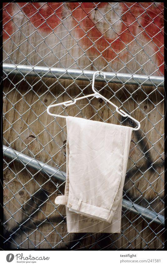 hose Mode Bekleidung Hose Stoff hängen warten Kleiderbügel Zaun Maschendrahtzaun Wand Graffiti Farbfoto Außenaufnahme