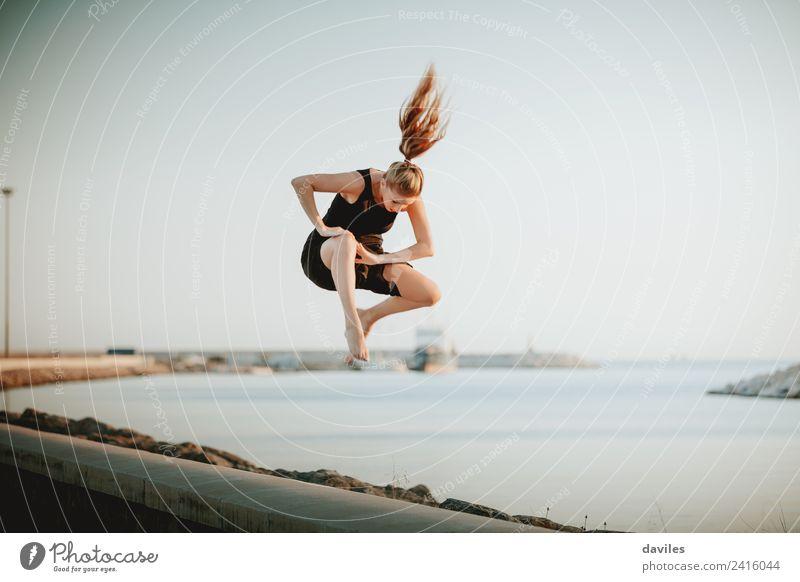 Blonde Frau, die in die Luft springt. Lifestyle Freude Freizeit & Hobby Handarbeit Ferien & Urlaub & Reisen Sonne Meer Tanzen Sport Mensch feminin Junge Frau