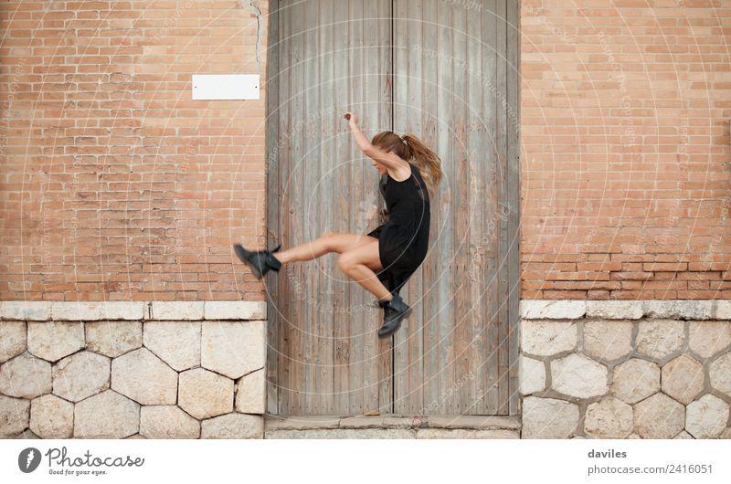 Blonde Frau in schwarzem Kleid tanzt und springt auf der Straße, vor einer alten Hausfassade. elegant Stil Entertainment Tanzen Mensch Junge Frau Jugendliche
