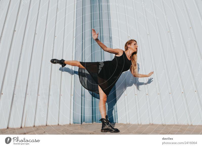 Blonde Frau im schwarzen Kleid tanzt, während sie ein Bein hochhebt. Lifestyle Körper Tanzen Sport Mensch feminin Erwachsene Jugendliche Arme 1 18-30 Jahre