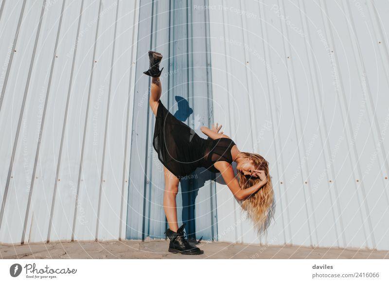 Blonde Frau führt zeitgenössischen Tanz auf, hebt ein Bein, gegen eine Wand. Lifestyle elegant Stil exotisch Sport Mensch Erwachsene Jugendliche 1 18-30 Jahre