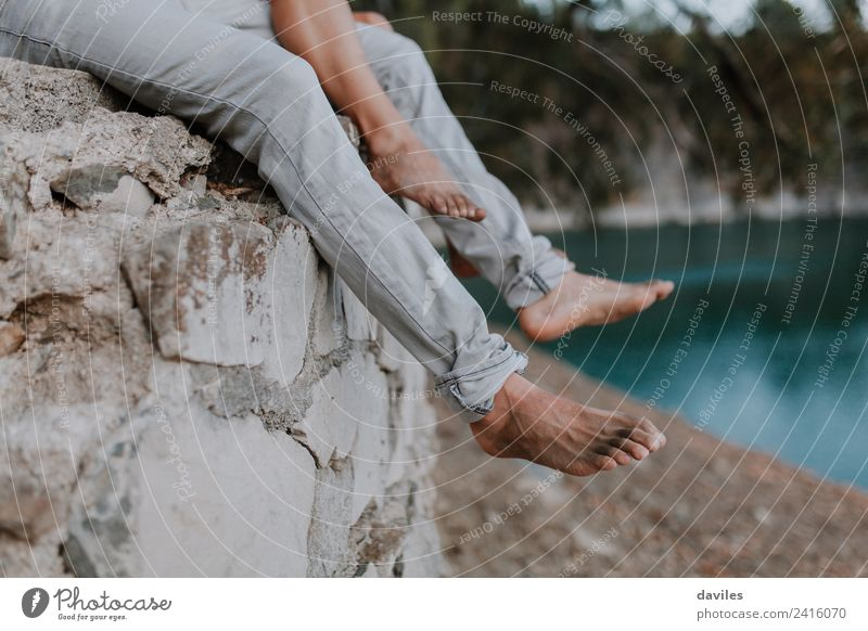 Beine von Mann und Frau an der Wand hängend Lifestyle Freizeit & Hobby Ferien & Urlaub & Reisen Mensch Erwachsene Paar Partner Fuß Natur See Fluss Jeanshose