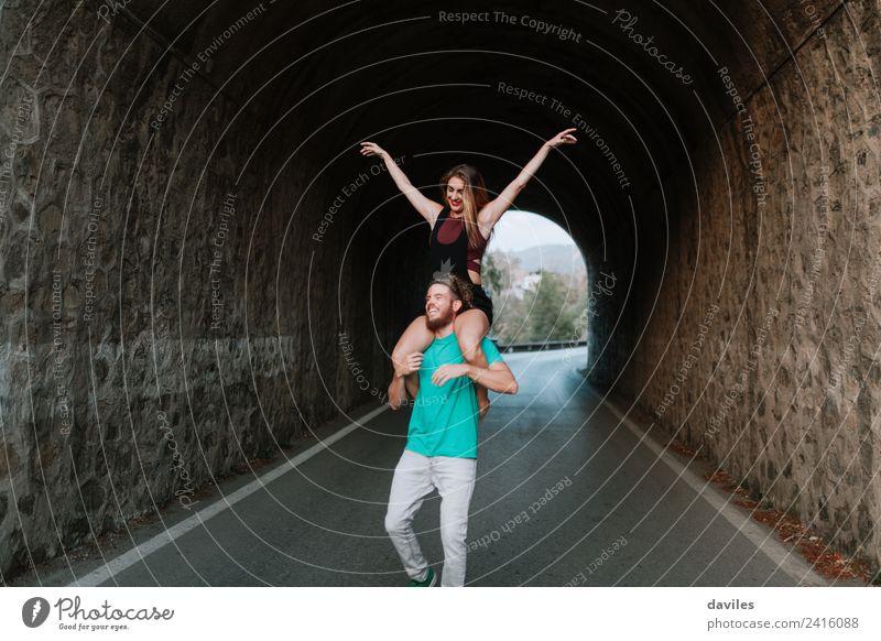 Ein glückliches junges Paar hat Spaß zusammen. Lifestyle Freude Ferien & Urlaub & Reisen Mensch Frau Erwachsene Mann 2 Straße Stein Lächeln Liebe tragen