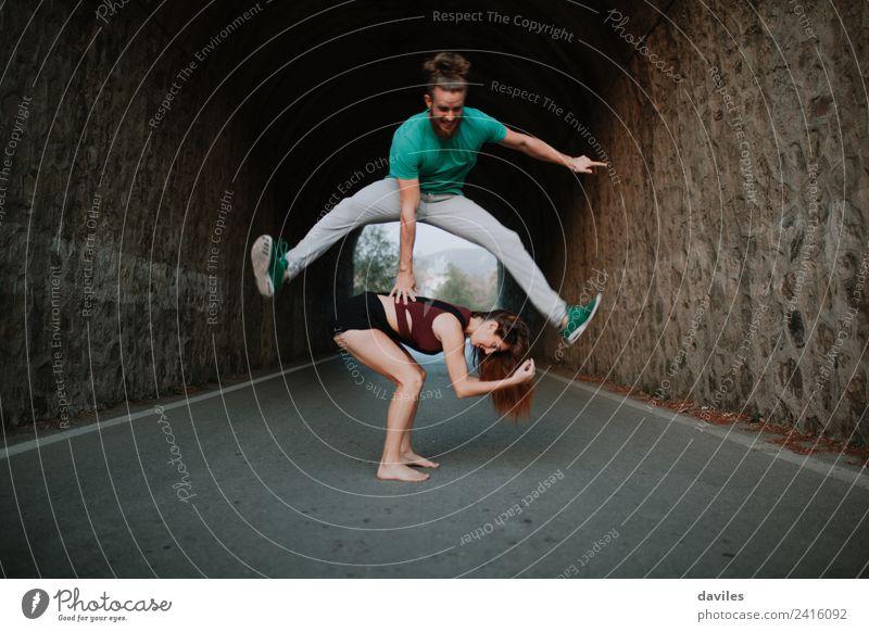 Mann springt über den Frosch und springt über eine Frau auf einer Straße. Freude Leben Spielen Freiheit Mensch Erwachsene Freundschaft Paar Jugendliche 2