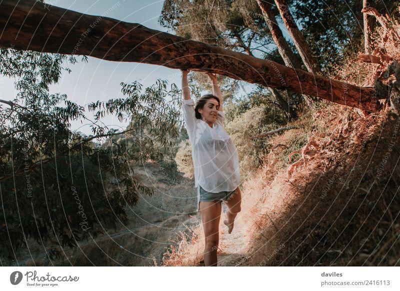 Lächelnde Frau, die in der Natur spazieren geht und an einem umgestürzten Baum hängt Lifestyle Berge u. Gebirge wandern Mensch Erwachsene 1 18-30 Jahre