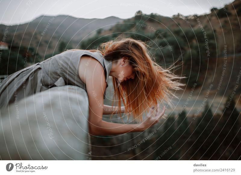 Frau lehnt sich an eine Brücke, während der Wind ihr Haar bewegt. Lifestyle schön Ferien & Urlaub & Reisen Tourismus Mensch Erwachsene 1 18-30 Jahre Jugendliche