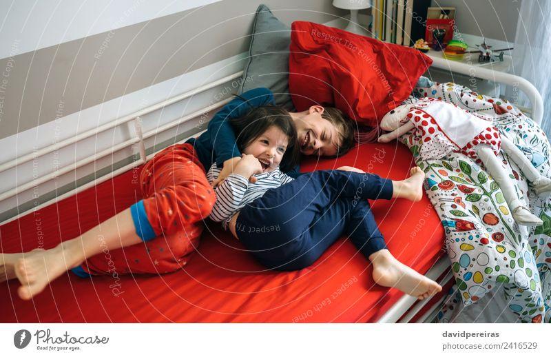 Brüder kitzeln und lachend liegend auf dem Bett. Lifestyle Freude Glück Spielen Schlafzimmer Kind Mensch Junge Frau Erwachsene Mann Schwester