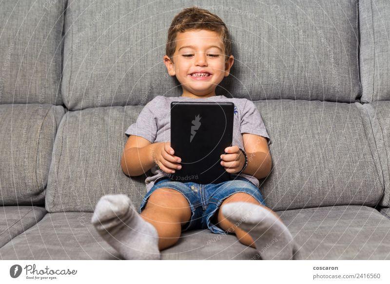 Kleiner Junge mit einem Tablett Glück Freizeit & Hobby Spielen Sofa Kind Schule Computer Notebook Bildschirm Technik & Technologie Internet Baby Kleinkind