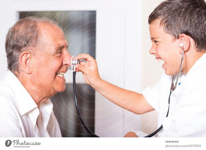Das Kind untersucht seinen Großvater mit dem Stethoskop. Gesicht Gesundheitswesen Krankheit Medikament Spielen Beruf Arzt Krankenhaus Karriere Mensch Junge
