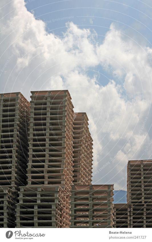 Im Zentrum der Hochstapler Hausbau Arbeitsplatz Paletten Personenverkehr Wirtschaft Handel Himmel Wolken Schönes Wetter Hochhaus Holz eckig hell hoch blau braun