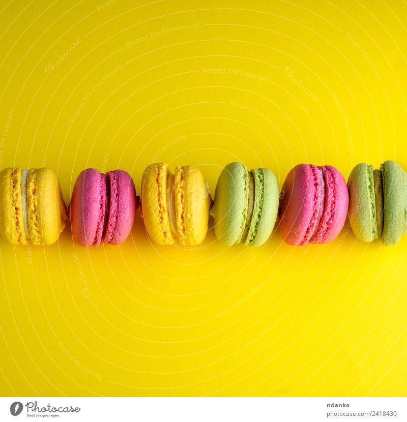 macarons liegt in einer Reihe in der Mitte. Dessert Süßwaren Essen hell gelb grün rosa Farbe Idee Macaron Hintergrund Lebensmittel farbenfroh Vanille