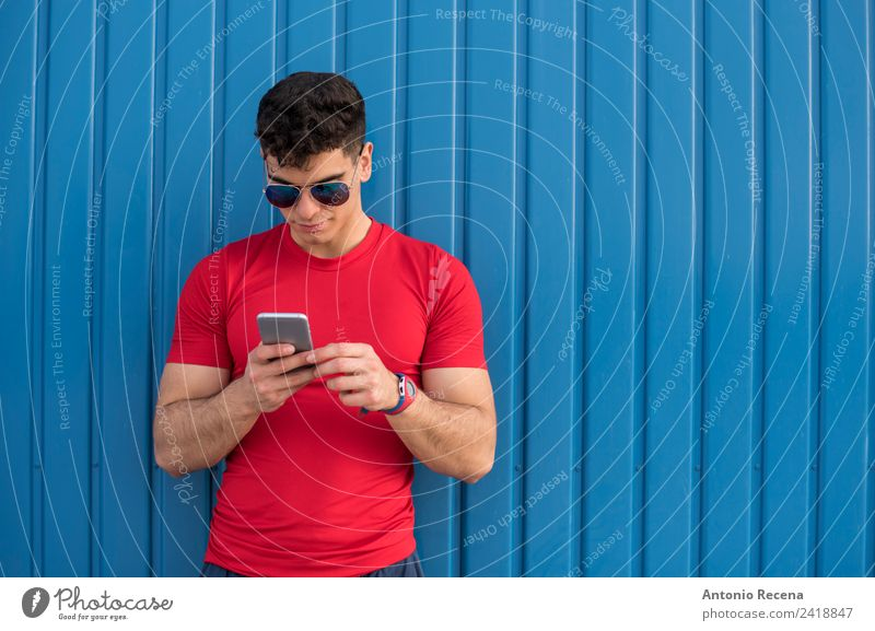 Rot sozial auf blauer Wand lesen Telefon PDA Mensch Mann Erwachsene Sonnenbrille brünett berühren rot 20-25 Jahre alt 20s 30 Jahre alt attraktiv Tür Latein
