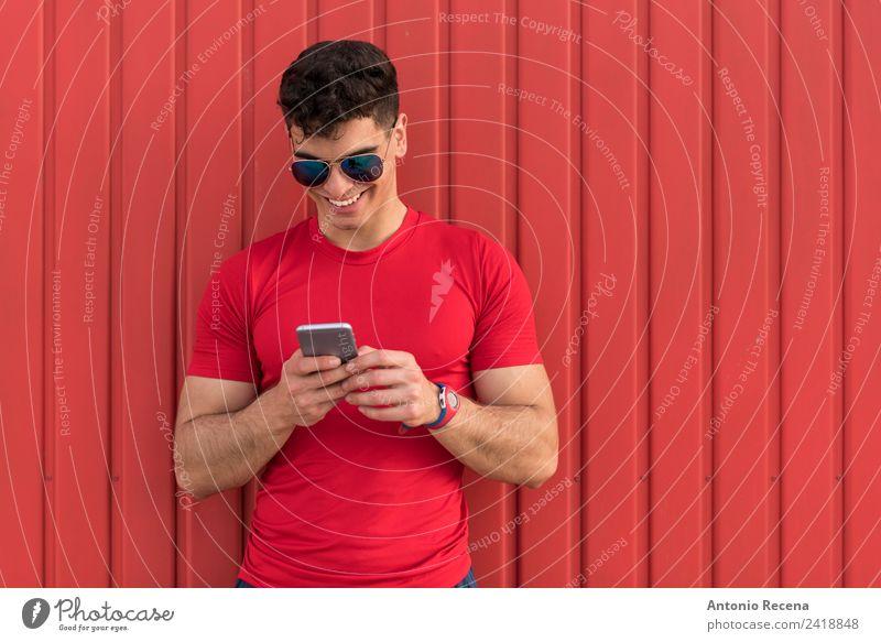 Mann auf Rot lesen Telefon Mensch Erwachsene Sonnenbrille brünett berühren Lächeln rot 20-25 Jahre alt 20s 30 Jahre alt attraktiv Tür Latein Lateinamerikaner