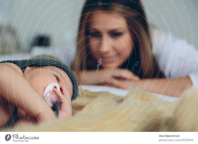 Baby schläft auf einer Decke, während ihre Mutter schaut. Glück schön Erholung ruhig Schlafzimmer Kind Mensch Frau Erwachsene Familie & Verwandtschaft Hut