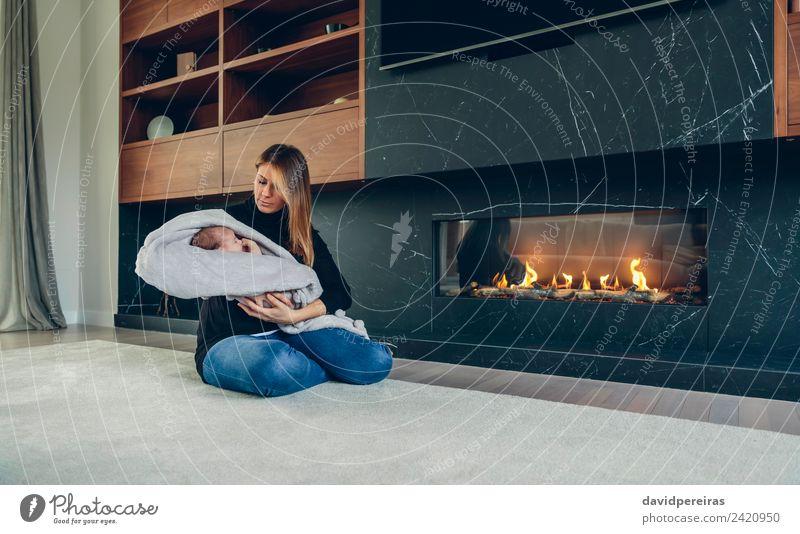 Mutter umarmt ihr Baby vor dem Kamin. Lifestyle Glück schön Möbel Wohnzimmer Kind Mensch Frau Erwachsene Familie & Verwandtschaft Wärme Lächeln Liebe schlafen