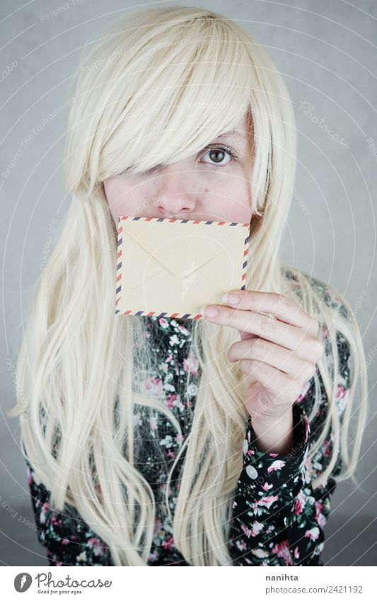 Junge blonde Frau, die ihren Mund mit einem Umschlag bedeckt. Design Haare & Frisuren Haut Gesicht Post Briefumschlag Adressat Einladung Absender Mensch feminin