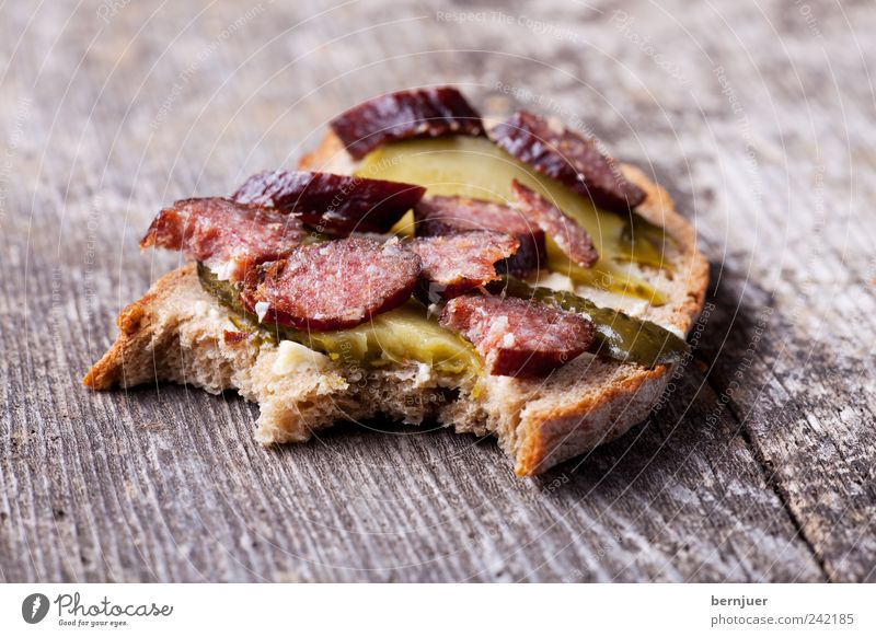 bites me Lebensmittel Wurstwaren Brot Ernährung Frühstück Holz ruhig Wurstbrot Brotscheibe Salami Gurkenscheibe Holzbrett Gewürzgurke beißen Snack landjaeger