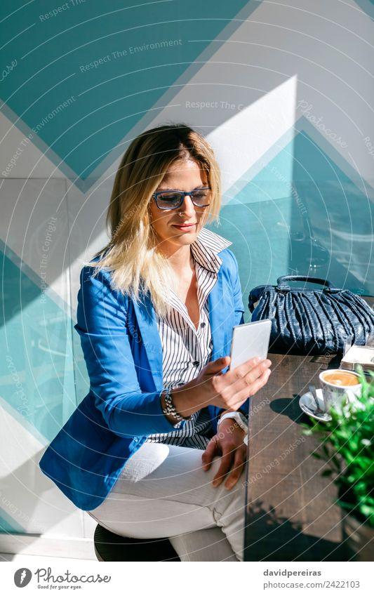Junge Frau beim Anschauen des Handys Kaffee Lifestyle kaufen schön Freizeit & Hobby lesen Tisch Arbeit & Erwerbstätigkeit Telefon PDA Technik & Technologie