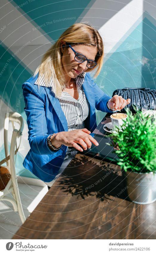 Mädchen, die Kaffee rührt und auf ihre Tablette schaut. Lifestyle kaufen schön Freizeit & Hobby lesen Tisch Arbeit & Erwerbstätigkeit Business Telefon PDA