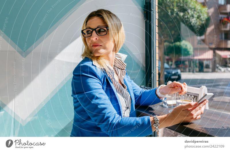 Junge Frau, die den Kaffee rührt, schaut zurück. Lifestyle kaufen schön Erholung Freizeit & Hobby Tisch Arbeit & Erwerbstätigkeit Telefon PDA