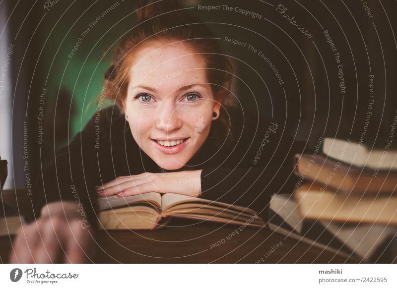 Innenporträt einer rothaarigen glücklichen Frau beim Lernen Lifestyle Erholung lesen Tisch Studium Erwachsene Buch Bibliothek Pullover lernen träumen dunkel