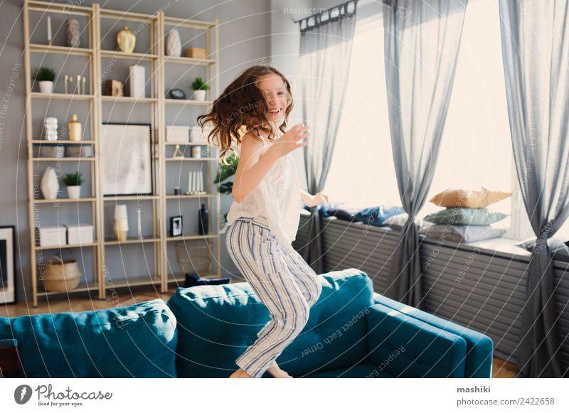 glückliches Kind Mädchen, das am Wochenendmorgen zu Hause spielt. Lifestyle Freude Leben Erholung Spielen Wohnung Familie & Verwandtschaft Kindheit springen