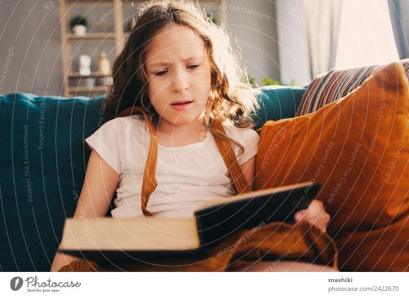 konzentriertes Kind Mädchen lesen interessantes Buch zu Hause Lifestyle Erholung Schulkind Kindheit Bibliothek authentisch klein klug heimwärts Bildung lernen