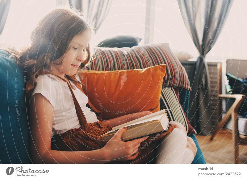 smartes Kind Mädchen liest interessantes Buch Lifestyle Erholung lesen Schule lernen Schulkind Kindheit Bibliothek authentisch klein klug Einsamkeit bequem