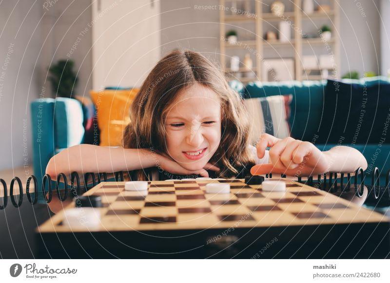 Lifestyle-Aufnahme von einem klugen Kind, das zu Hause Dame spielt. Freizeit & Hobby Spielen Schach Erfolg Mädchen Familie & Verwandtschaft Kindheit Spielzeug