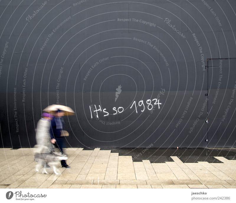 depressive Mensch Paar Partner 2 schlechtes Wetter Regen Mauer Wand Fußgänger Tier Haustier Hund Schriftzeichen Graffiti grau Zukunftsangst Endzeitstimmung