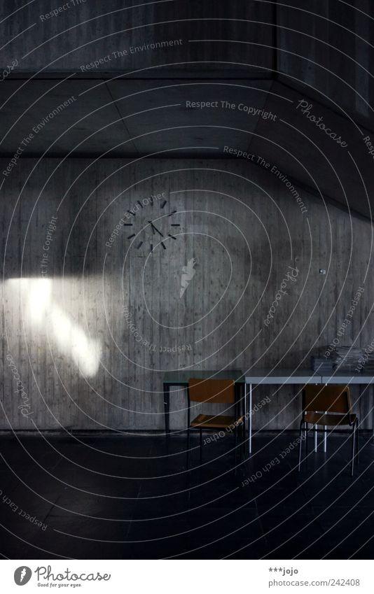 17:23. Beton trist Zeit Uhr Wanduhr Betonwand betoniert Betonklotz Studium Zifferblatt Stuhl Tisch Menschenleer dunkel Nachmittag Nachmittagssonne Lichtfleck