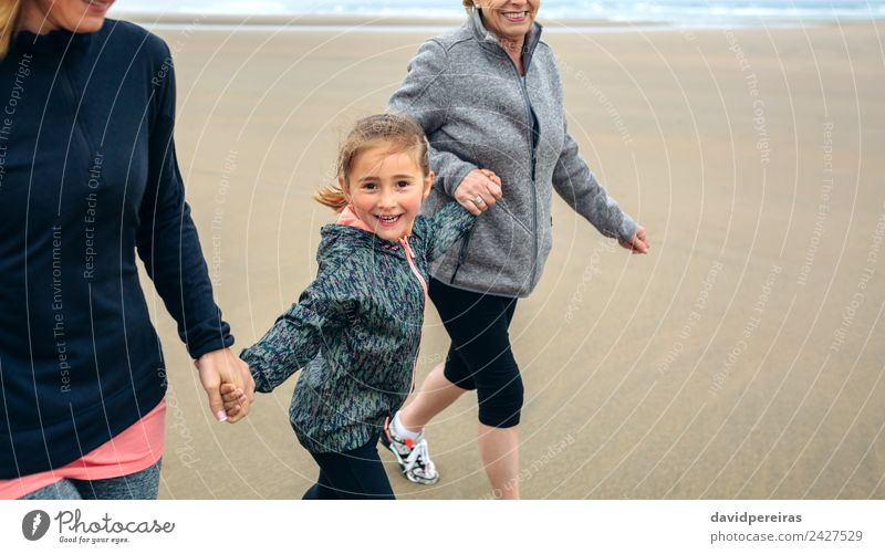 Kleines Mädchen läuft mit Frauen am Strand Lifestyle Freude Glück Spielen Kind Mensch Erwachsene Mutter Großmutter Familie & Verwandtschaft Sand Herbst Nebel