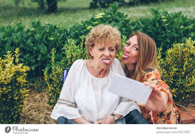 Frau nimmt Selfie mit älterer Mutter im Rollstuhl Lifestyle Freude Glück Gesundheitswesen Garten PDA Mensch Erwachsene Großmutter Familie & Verwandtschaft Natur