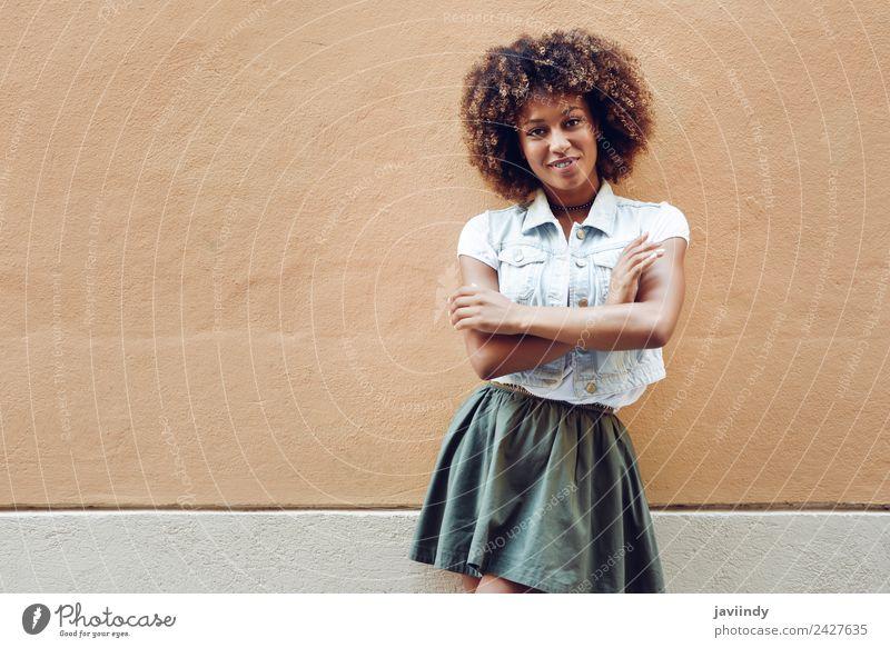Junge schwarze Frau, Afro-Frisur, lächelnd in der Nähe einer Mauer auf der Straße Lifestyle Stil Glück schön Haare & Frisuren Gesicht Mensch Junge Frau