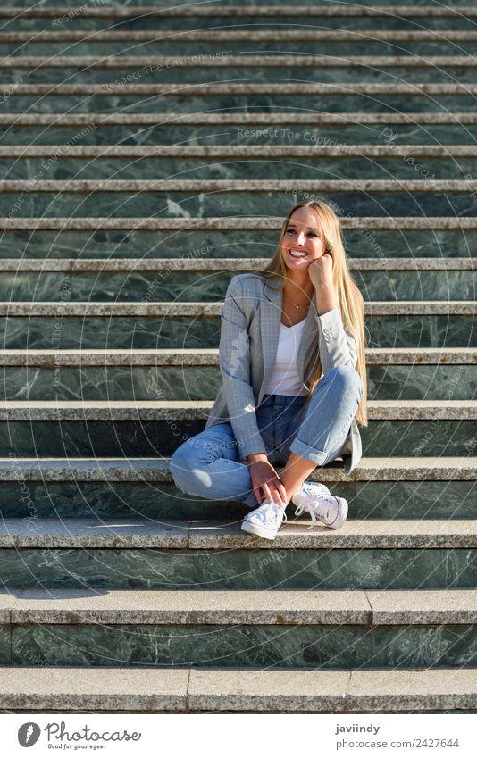 Blonde Frau lächelnd im urbanen Hintergrund Lifestyle Stil Glück schön Haare & Frisuren Mensch Erwachsene Herbst Straße Mode Bekleidung Jeanshose Jacke blond