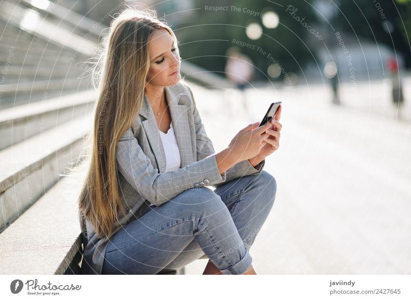 Blonde Frau, die ihr Smartphone im Freien ansieht. Lifestyle Stil schön Haare & Frisuren Telefon PDA Mensch Junge Frau Jugendliche Erwachsene 1 18-30 Jahre