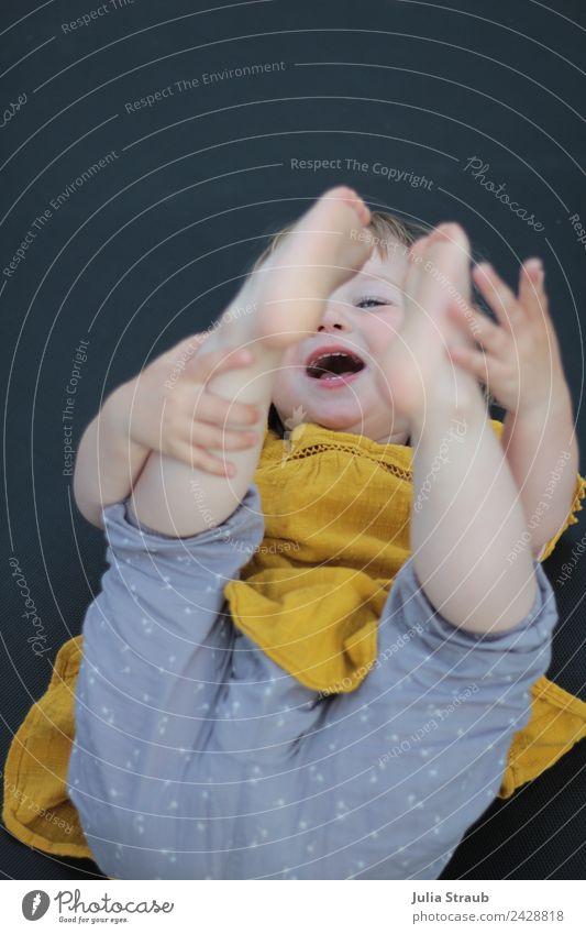 Kleinkind Trampolin lachen Füße Hände liegen feminin Kindheit 1 Mensch 1-3 Jahre Hose Kleid Fröhlichkeit lustig gelb grau schwarz Freude Lebensfreude Farbfoto