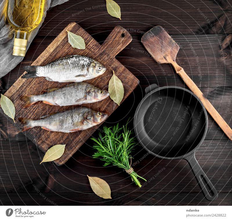 drei Flussfische auf einem braunen Holzbrett Fisch Meeresfrüchte Kräuter & Gewürze Ernährung Abendessen Diät Pfanne Tisch Essen dunkel frisch oben retro schwarz