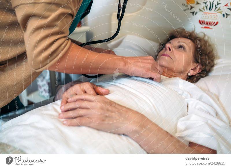 Betreuerin, die eine ältere Frau auskultiert. Lifestyle Gesundheitswesen Krankheit Medikament Haus Arzt Krankenhaus Mensch Erwachsene Herz alt hören authentisch