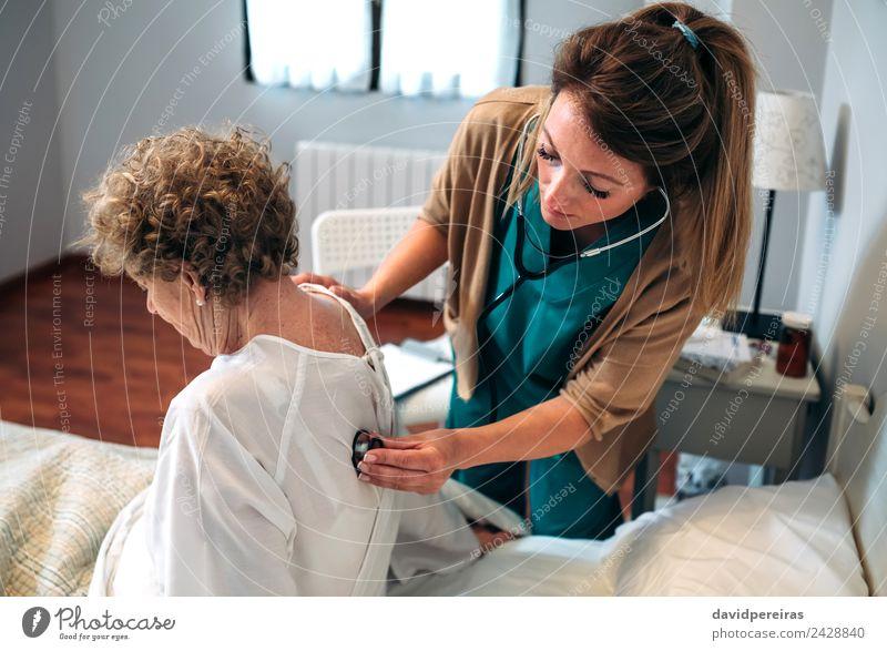 Betreuerin, die eine ältere Frau auskultiert. Gesundheitswesen Krankheit Medikament Haus Lampe Stuhl Arzt Krankenhaus Mensch Erwachsene Herz alt hören
