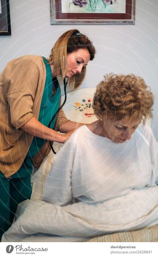 Betreuerin, die eine ältere Frau auskultiert. Gesundheitswesen Krankheit Medikament Haus Lampe Arzt Krankenhaus Mensch Erwachsene Herz alt hören authentisch