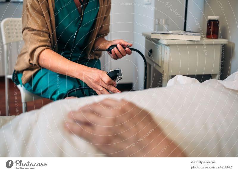 Betreuerin, die den Blutdruck einer älteren Frau überprüft. Gesundheitswesen Medikament Haus Stuhl Prüfung & Examen Arzt Krankenhaus Mensch Erwachsene Hand alt