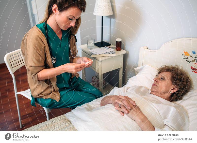 Arzt misst die Temperatur der älteren Frau Gesundheitswesen Krankheit Medikament Haus Stuhl Krankenhaus Mensch Erwachsene alt authentisch Haushaltshilfe