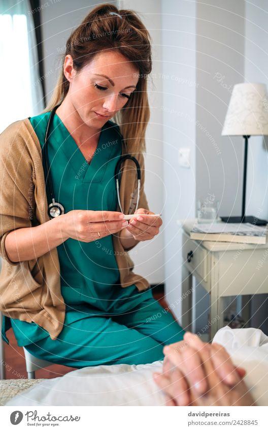 Arzt misst die Temperatur der älteren Frau Gesundheitswesen Krankheit Medikament lesen Haus Stuhl Krankenhaus Mensch Erwachsene alt authentisch Thermometer