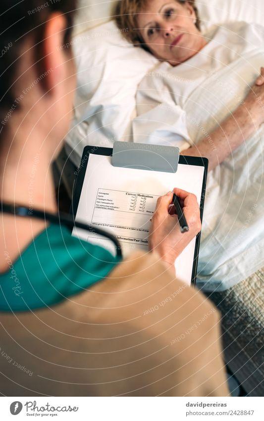 Ärztin beim Ausfüllen eines Fragebogens Gesundheitswesen Behandlung Krankheit Haus Arzt Krankenhaus Mensch Frau Erwachsene Schreibstift alt authentisch